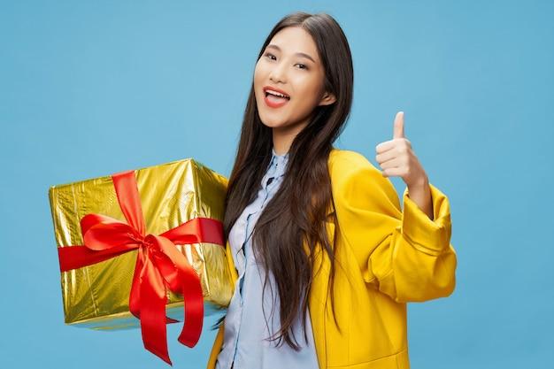 Donna asiatica con scatola regalo d'oro, pollice in alto