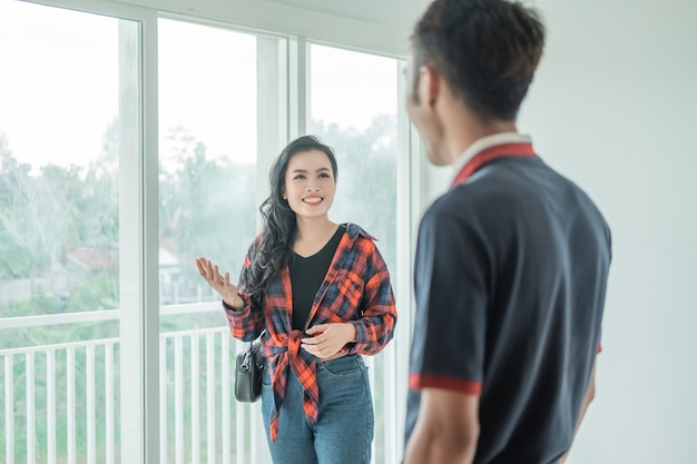 Donna asiatica con gesto della mano in chat con lo sviluppatore immobiliare mentre esplora le stanze