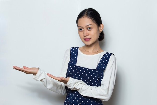 Donna asiatica con punto della mano su uno spazio vuoto