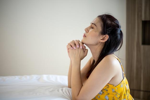 Donna asiatica con la mano che prega, le mani giunte in preghiera sul letto. concetto di fede, spiritualità e religione.
