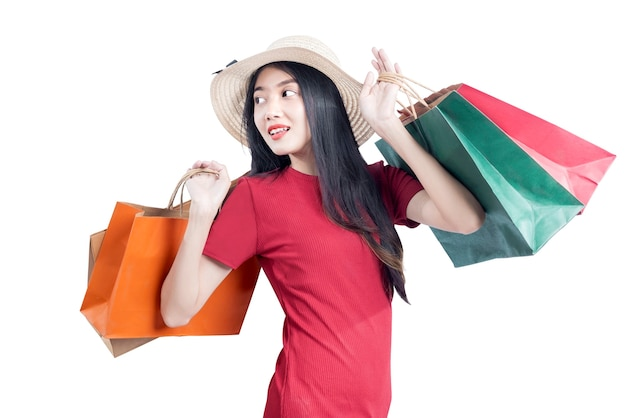 Donna asiatica con il cappello che trasportano borse della spesa isolate su sfondo bianco