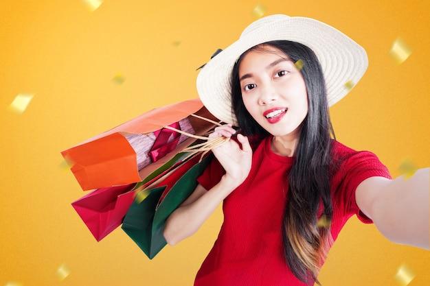 Donna asiatica con il cappello che trasportano le borse della spesa e prendendo selfie sulla vendita di fine anno. felice anno nuovo 2021