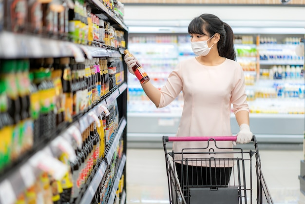 Donna asiatica con maschera igienica e guanto di gomma con carrello della spesa in cerca di salsa o aroma da acquistare durante l'epidemia di covid-19 per la preparazione per una quarantena di pandemia