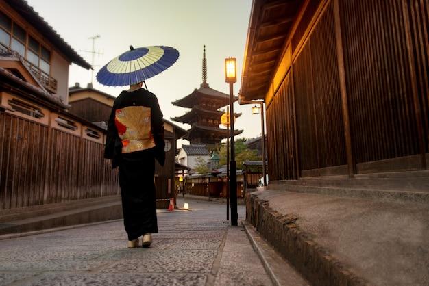 Donna asiatica con kimono che cammina alla pagoda di yasaka a kyoto