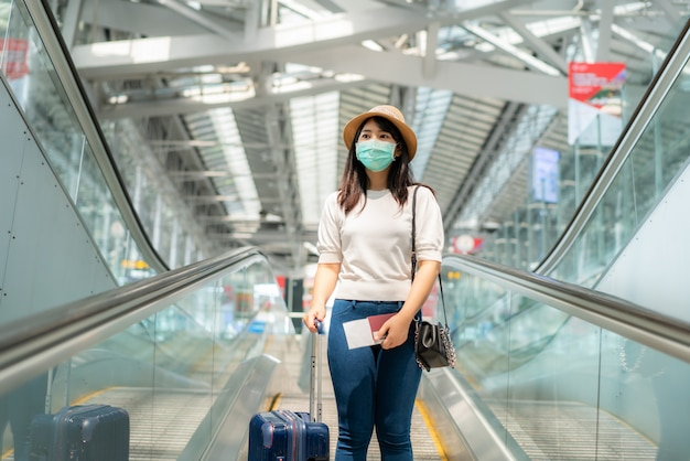 Donna asiatica con la maschera da portare dei bagagli