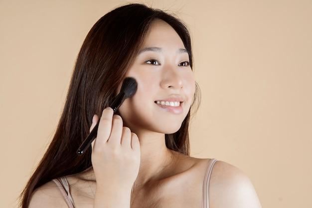 Donna asiatica con pennello per il trucco su sfondo semplice