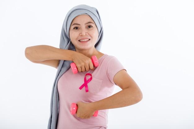 Una donna asiatica con nastro rosa per la consapevolezza del cancro al seno tiene un manubrio isolato su sfondo rosa spazio copia vuoto, assistenza sanitaria, concetto di medicina
