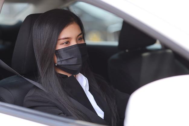 Donna asiatica con maschera protettiva in automobile e guida di auto.
