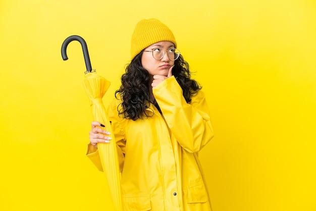 Donna asiatica con cappotto antipioggia e ombrello isolato su sfondo giallo con dubbi