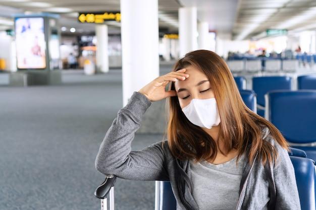 Donna asiatica con una maschera chirurgica in attesa in aeroporto