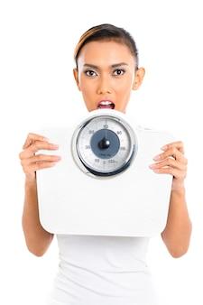 Donna asiatica con la scala del peso che perde peso
