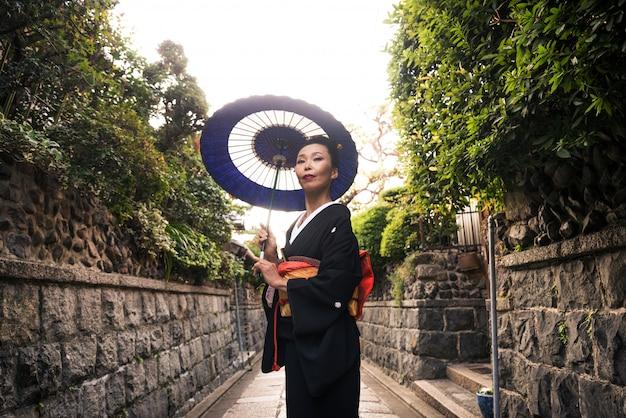 Donna asiatica con yukata che cammina a kyoto, giappone