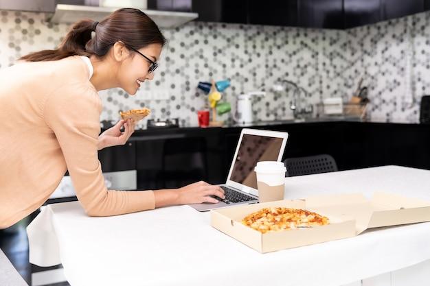 La donna asiatica lavora da casa in cucina e mangia pizza a domicilio
