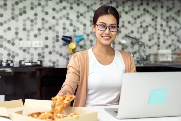 La donna asiatica lavora da casa in cucina con la consegna da asporto