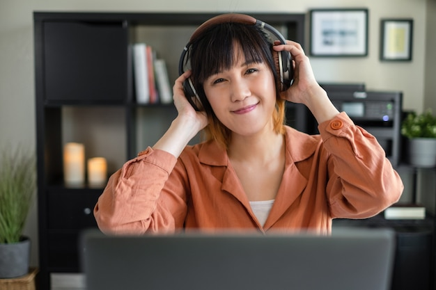 Lavoro asiatico della donna con il computer a casa. ascolto lezione online. programma audio con cuffia.
