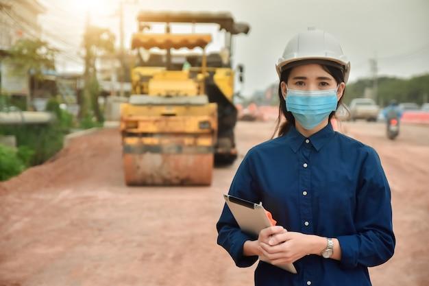 Lavoratore donna asiatica in maschera tenendo la compressa