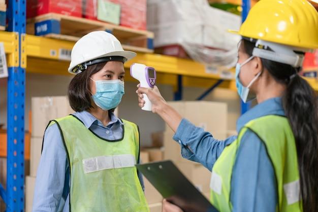 La lavoratrice asiatica indossa la maschera per il viso nel giubbotto di sicurezza utilizzando la scansione a infrarossi del termometro per controllare la temperatura corporea con il collega prima di lavorare nella fabbrica del magazzino durante la pandemia di coronavirus