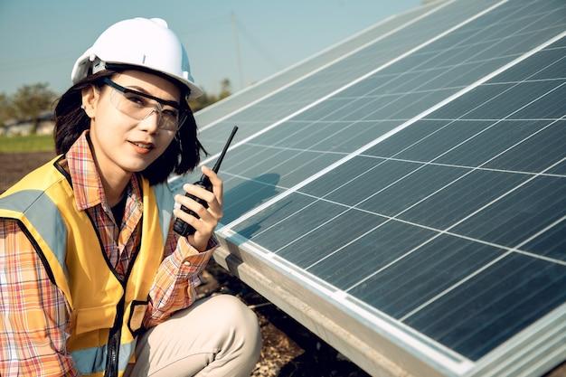 Tecnici delle lavoratrici asiatiche che tengono walkie-talkie e controllano l'installazione di pesanti pannelli solari fotovoltaici