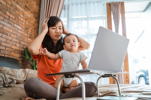 Donna asiatica che lavora mentre prendersi cura dei bambini