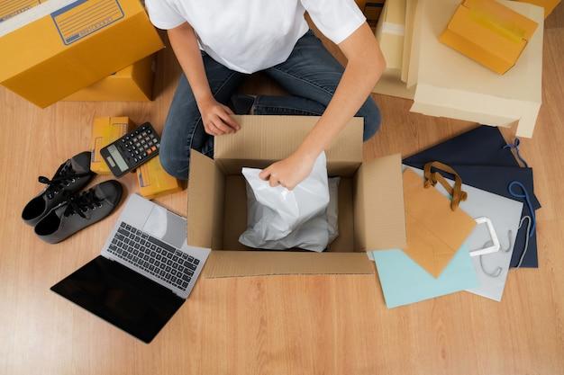 Donna asiatica che lavora con una scatola di prodotto, vendita di idee online concetto, negozio online di affari del venditore a casa
