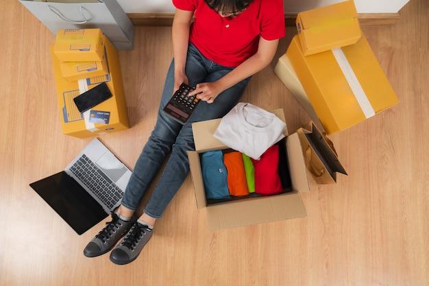 Donna asiatica che lavora con la calcolatrice, concetto di vendita di idee in linea, negozio di affari del venditore in linea a casa