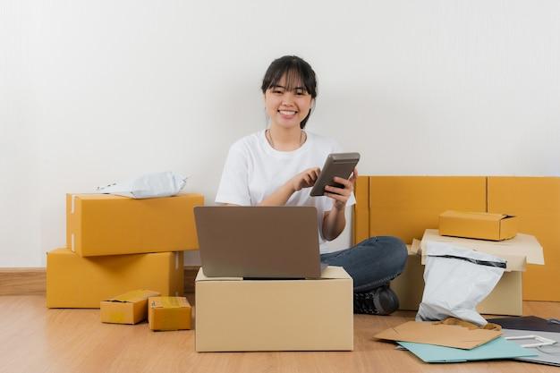 Donna asiatica che lavora con la calcolatrice, vendita di idee in linea concetto, negozio di affari del venditore in linea a casa
