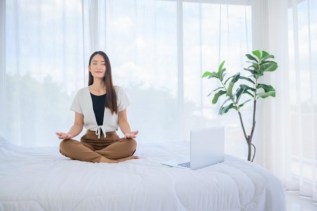 Donna asiatica yoga respirazione e meditazione da sola a casa. rilassante per uno stile di vita sano a letto. attività sportiva e ricreativa indoor.