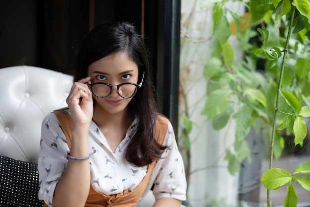 Le donne asiatiche stanno tenendo i vetri e stanno sorridendo ad una caffetteria in vacanza.