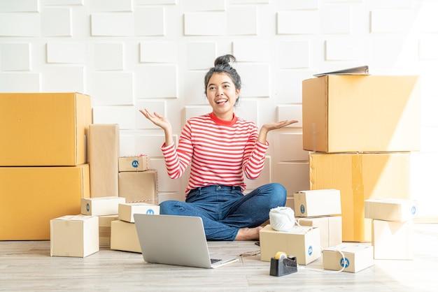 Imprenditore di donne asiatiche che lavora a casa con scatola di imballaggio sul posto di lavoro - imprenditore di pmi dello shopping online o concetto di vendita online