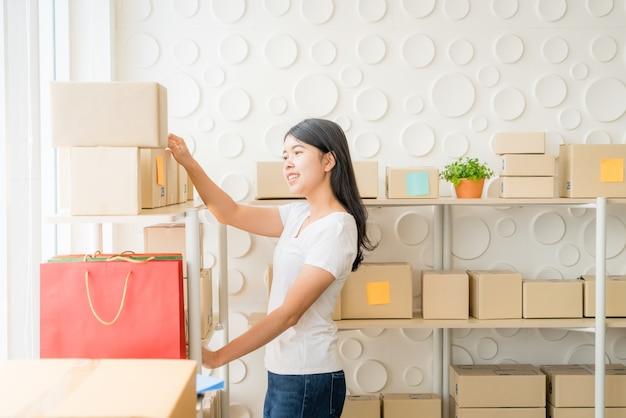 Imprenditore di donne asiatiche lavora a casa con scatola di imballaggio sul posto di lavoro