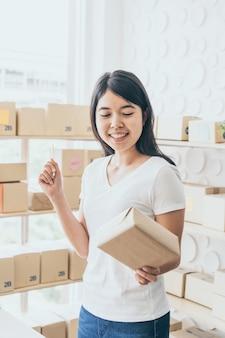 Imprenditore asiatico delle donne che lavora a casa con il contenitore di imballaggio sul posto di lavoro