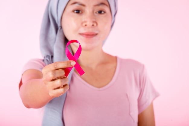 Un malato di cancro mammario di malattia delle donne asiatiche in pullover che tiene nastro rosa isolato su fondo dello studio dello spazio della copia in bianco rosa, sanità, concetto della medicina