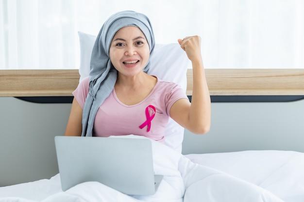 Una donna asiatica malata di cancro mammario con nastro rosa che indossa il velo dopo il trattamento alla chemioterapia con lavoro di lavoro al computer portatile sul letto nella camera da letto a casa, assistenza sanitaria, medicina