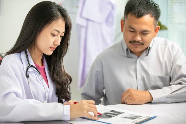 Discussione paziente del medico e dell'uomo delle donne asiatiche sulle immagini dei raggi x dei risultati nell'ufficio della clinica