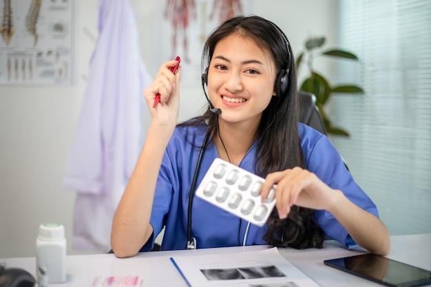 Il medico delle donne asiatiche parla tramite chat video consultando il paziente online sui sintomi e sui farmaci