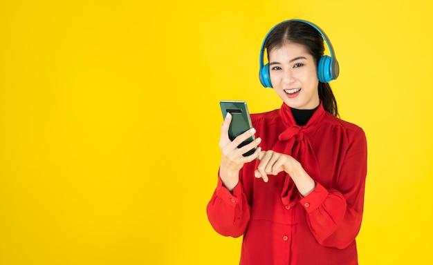 Le donne asiatiche di buon umore tengono il telefono e indossano le cuffie senza fili nel vestito rosso.