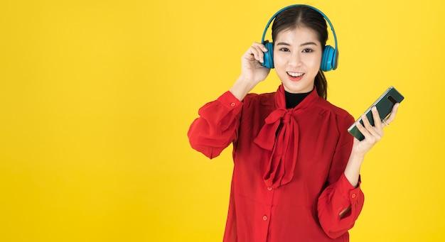 Le donne asiatiche di buon umore tengono il telefono e mettono le cuffie senza fili con il vestito rosso.