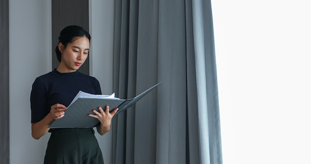 Donne asiatiche in possesso di file e revisione di documenti per lavorare in ufficio