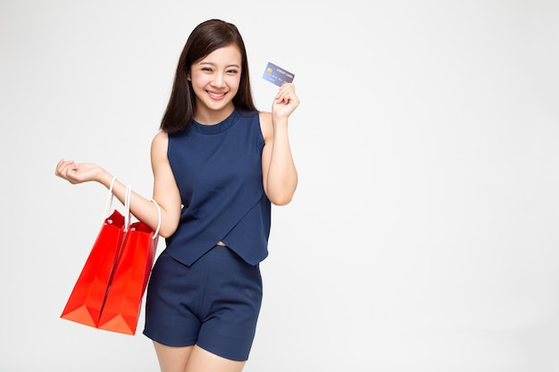 Donne asiatiche che tengono i sacchetti della spesa e la carta di credito