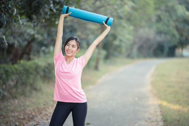 Le donne asiatiche in possesso di materassini da yoga faranno yoga al parco per rimanere in salute e avere una buona forma.