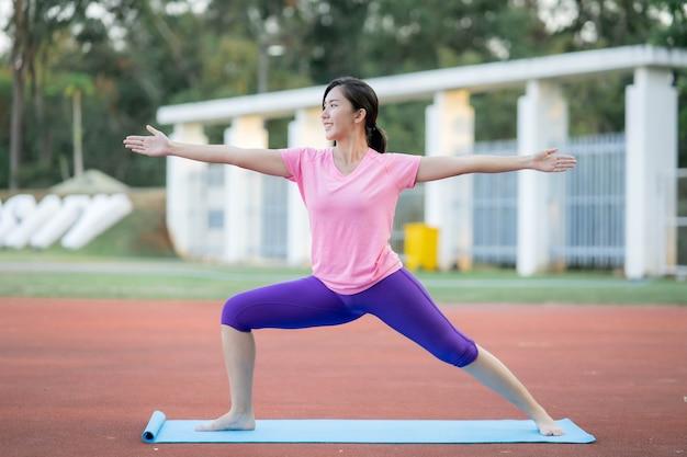 Le donne asiatiche in possesso di tappetini da yoga faranno yoga al parco per mantenersi in salute e avere una buona forma.