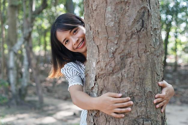 Donne asiatiche che abbracciano gli alberi, concetto di amore per il mondo