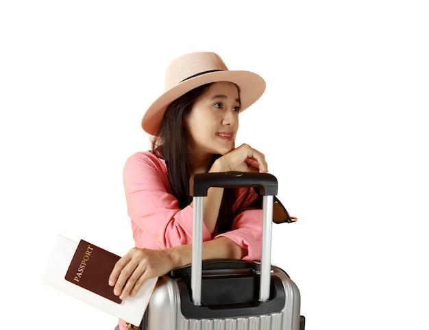 I capelli lunghi delle donne asiatiche indossano il cappello di paglia in mano che tiene il libro del passaporto e gli occhiali da sole