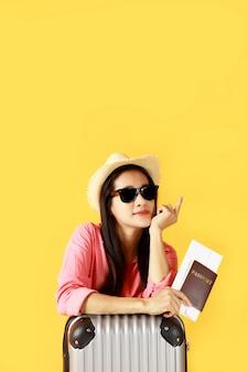 Capelli lunghi delle donne asiatiche indossano cappello di paglia, occhiali da sole in mano che tiene il passaporto