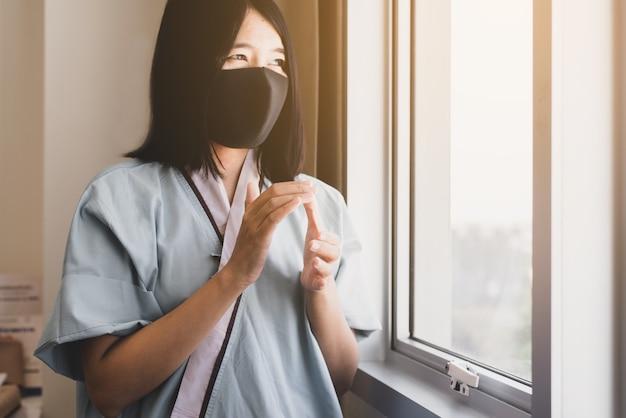 Pazienti asiatiche che applaudono per sostenere le persone che combattono il coronavirus attraverso la finestra dell'ospedale