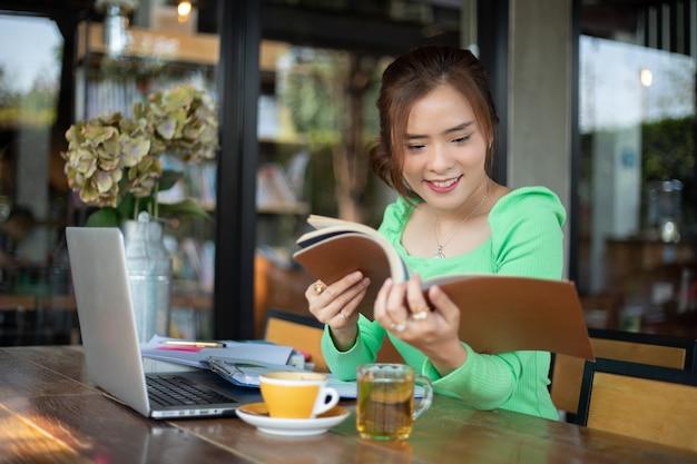Libro di lettura asiatico delle donne e sorridere e rilassarsi felice in una caffetteria dopo aver lavorato in un riuscito ufficio.