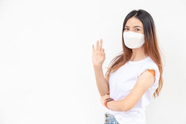 Le donne asiatiche mostrano la fasciatura sul braccio. felice donna asiatica si sente bene dopo aver ricevuto il vaccino su sfondo bianco.