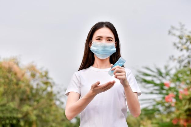 Le donne asiatiche usano le mani detergenti con gel alcolico per proteggere il coronavirus covid19