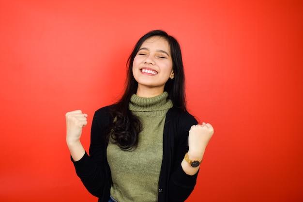 Donne asiatiche che usano un maglione nero che mostrano gesto eccitato e felice con sfondo rosso isolato