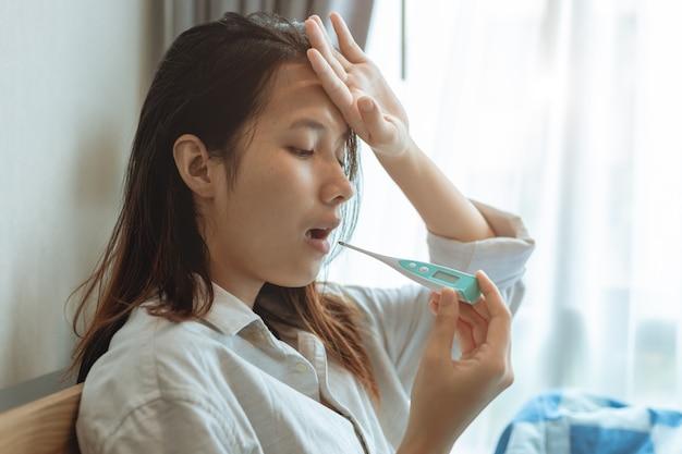 Le donne asiatiche che utilizzano il termometro per test orale misurano la temperatura corporea per diagnosticare l'influenza da infezione da coronavirus.